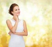 Χαμογελώντας γυναίκα στο άσπρο φόρεμα που φορά το δαχτυλίδι διαμαντιών Στοκ Εικόνες