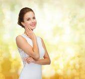 Χαμογελώντας γυναίκα στο άσπρο φόρεμα που φορά το δαχτυλίδι διαμαντιών Στοκ Φωτογραφίες
