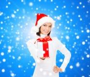 Χαμογελώντας γυναίκα στο καπέλο αρωγών santa με το κιβώτιο δώρων Στοκ Εικόνα