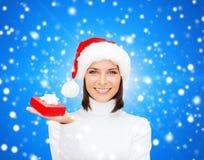 Χαμογελώντας γυναίκα στο καπέλο αρωγών santa με το κιβώτιο δώρων Στοκ Εικόνες
