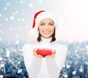 Χαμογελώντας γυναίκα στο καπέλο αρωγών santa με το κιβώτιο δώρων Στοκ Φωτογραφία