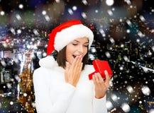 Χαμογελώντας γυναίκα στο καπέλο αρωγών santa με το κιβώτιο δώρων Στοκ Φωτογραφίες