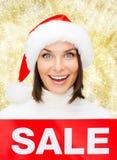 Χαμογελώντας γυναίκα στο καπέλο αρωγών santa με το σημάδι πώλησης Στοκ Φωτογραφία