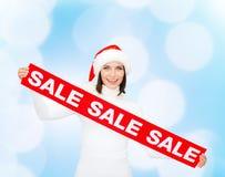 Χαμογελώντας γυναίκα στο καπέλο αρωγών santa με το σημάδι πώλησης Στοκ εικόνα με δικαίωμα ελεύθερης χρήσης