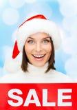 Χαμογελώντας γυναίκα στο καπέλο αρωγών santa με το σημάδι πώλησης Στοκ εικόνες με δικαίωμα ελεύθερης χρήσης