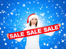 Χαμογελώντας γυναίκα στο καπέλο αρωγών santa με το σημάδι πώλησης Στοκ φωτογραφίες με δικαίωμα ελεύθερης χρήσης
