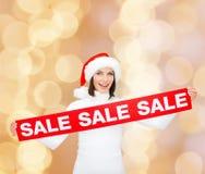 Χαμογελώντας γυναίκα στο καπέλο αρωγών santa με το σημάδι πώλησης Στοκ Εικόνα