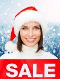 Χαμογελώντας γυναίκα στο καπέλο αρωγών santa με το σημάδι πώλησης Στοκ Εικόνες
