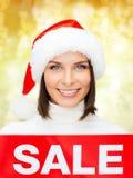 Χαμογελώντας γυναίκα στο καπέλο αρωγών santa με το σημάδι πώλησης Στοκ φωτογραφία με δικαίωμα ελεύθερης χρήσης