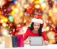 Χαμογελώντας γυναίκα στο καπέλο αρωγών santa με το PC ταμπλετών Στοκ Φωτογραφίες