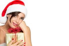 Χαμογελώντας γυναίκα στο καπέλο Santa με ένα χριστουγεννιάτικο δώρο Στοκ Εικόνες