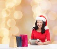 Χαμογελώντας γυναίκα στο καπέλο santa με τις τσάντες και το PC ταμπλετών Στοκ Εικόνα