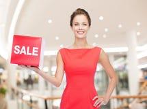 Χαμογελώντας γυναίκα στο κόκκινο καπέλο φορεμάτων με το σημάδι πώλησης Στοκ Φωτογραφία