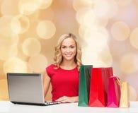 Χαμογελώντας γυναίκα στο κόκκινο πουκάμισο με τα δώρα και το lap-top Στοκ εικόνα με δικαίωμα ελεύθερης χρήσης
