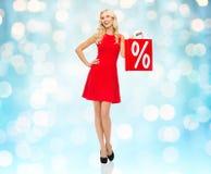 Χαμογελώντας γυναίκα στο κόκκινο φόρεμα με την τσάντα αγορών Στοκ Εικόνες