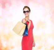 Χαμογελώντας γυναίκα στο κόκκινο φόρεμα με τις τσάντες αγορών Στοκ εικόνες με δικαίωμα ελεύθερης χρήσης