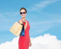 Χαμογελώντας γυναίκα στο κόκκινο φόρεμα με τις τσάντες αγορών Στοκ εικόνα με δικαίωμα ελεύθερης χρήσης