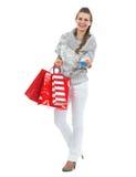 Χαμογελώντας γυναίκα στο πουλόβερ με την τσάντα αγορών Χριστουγέννων που δίνει την πιστωτική κάρτα Στοκ Εικόνες