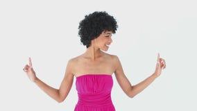 Χαμογελώντας γυναίκα στο ροζ που δείχνει επάνω απόθεμα βίντεο
