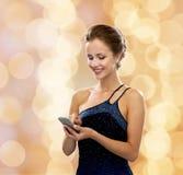Χαμογελώντας γυναίκα στο φόρεμα βραδιού με το smartphone Στοκ Εικόνες