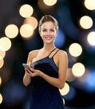 Χαμογελώντας γυναίκα στο φόρεμα βραδιού με το smartphone Στοκ Εικόνα
