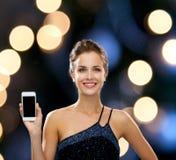 Χαμογελώντας γυναίκα στο φόρεμα βραδιού με το smartphone Στοκ Φωτογραφίες