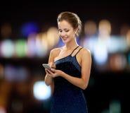 Χαμογελώντας γυναίκα στο φόρεμα βραδιού με το smartphone Στοκ Φωτογραφία