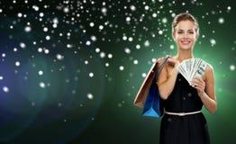 Χαμογελώντας γυναίκα στο φόρεμα με τις τσάντες αγορών Στοκ Φωτογραφίες