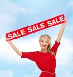 Χαμογελώντας γυναίκα στο φόρεμα με το κόκκινο σημάδι πώλησης Στοκ φωτογραφία με δικαίωμα ελεύθερης χρήσης
