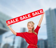 Χαμογελώντας γυναίκα στο φόρεμα με το κόκκινο σημάδι πώλησης Στοκ Εικόνες