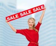 Χαμογελώντας γυναίκα στο φόρεμα με το κόκκινο σημάδι πώλησης Στοκ Φωτογραφία