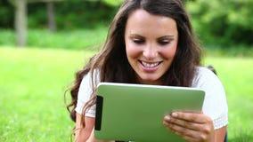 Χαμογελώντας γυναίκα σχετικά με έναν υπολογιστή ταμπλετών απόθεμα βίντεο