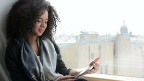 Χαμογελώντας γυναίκα brunette που εργάζεται με μια ψηφιακή ταμπλέτα απόθεμα βίντεο