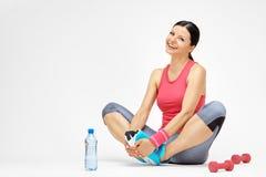 Χαμογελώντας γυναίκα brunette που κάνει τις τεντώνοντας ασκήσεις στη γυμναστική Στοκ Φωτογραφία