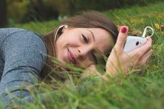 Χαμογελώντας γυναίκα brunnette που χρησιμοποιεί το τηλέφωνο κυττάρων Στοκ Εικόνες
