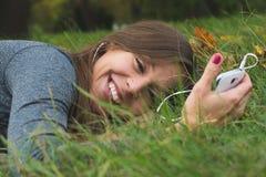 Χαμογελώντας γυναίκα brunnette που χρησιμοποιεί το τηλέφωνο κυττάρων Στοκ Φωτογραφίες