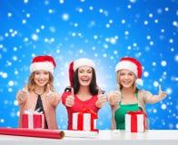 Χαμογελώντας γυναίκες στα καπέλα αρωγών santa που συσκευάζουν τα δώρα Στοκ εικόνα με δικαίωμα ελεύθερης χρήσης