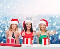 Χαμογελώντας γυναίκες στα καπέλα αρωγών santa που συσκευάζουν τα δώρα Στοκ Εικόνες