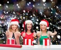 Χαμογελώντας γυναίκες στα καπέλα αρωγών santa που συσκευάζουν τα δώρα Στοκ Εικόνα