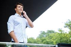 Χαμογελώντας επιτυχής νέος επιχειρηματίας που μιλά στο τηλέφωνο κυττάρων Στοκ εικόνα με δικαίωμα ελεύθερης χρήσης