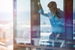 Χαμογελώντας επιχειρηματίας μέσα στο γραφείο και ομιλία στο τηλέφωνο κυττάρων Στοκ Εικόνες