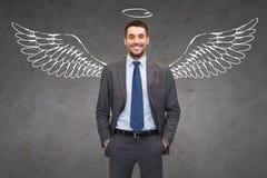 Χαμογελώντας επιχειρηματίας με τα φτερά και Nimbus αγγέλου στοκ φωτογραφία