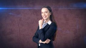 Χαμογελώντας επιχειρηματίας με τα όπλα που διπλώνονται εξέταση σας Στάση πέρα από το καφετί υπόβαθρο Στοκ Εικόνες