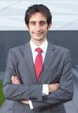 Χαμογελώντας επιχειρηματίας με τη μαύρη τρίχα και τα διασχισμένα όπλα Στοκ Εικόνα