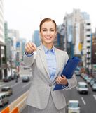 Χαμογελώντας επιχειρηματίας με το φάκελλο και τα κλειδιά Στοκ Φωτογραφία