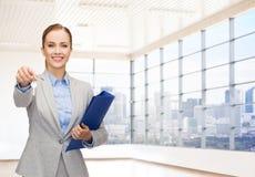 Χαμογελώντας επιχειρηματίας με το φάκελλο και τα κλειδιά Στοκ Εικόνες