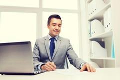 Χαμογελώντας επιχειρηματίας με το lap-top και τα έγγραφα Στοκ Φωτογραφίες