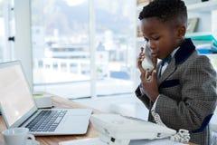 Χαμογελώντας επιχειρηματίας με το lap-top που χρησιμοποιεί το τηλέφωνο στο γραφείο Στοκ Φωτογραφία