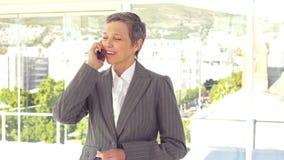 Χαμογελώντας επιχειρηματίας που έχει ένα τηλεφώνημα απόθεμα βίντεο