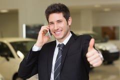 Χαμογελώντας επιχειρηματίας που δίνει τους αντίχειρες επάνω στο τηλέφωνο Στοκ Εικόνες